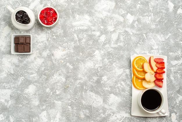 Vista de cima frutas frescas com uma xícara de café e geléia no fundo branco.