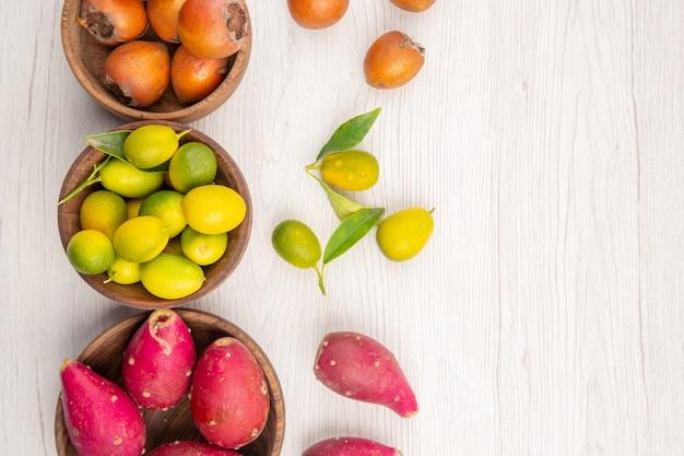 Vista de cima frutas frescas diferentes dentro de pratos no fundo branco dieta madura tropical exótica cor vida saudável espaço livre