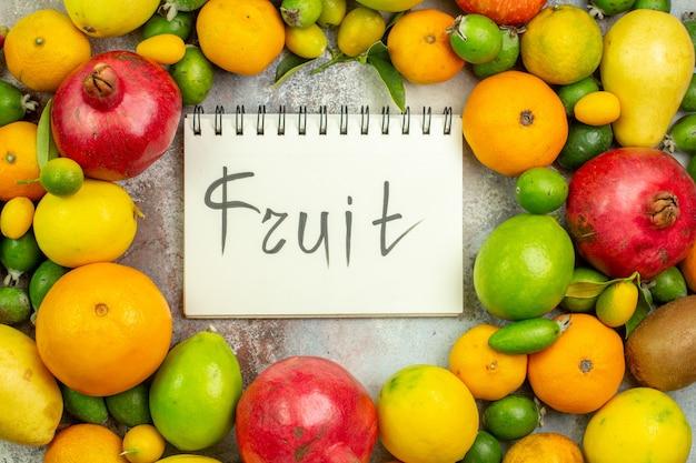Vista de cima frutas frescas diferentes frutas maduras com frutas escritas no bloco de notas no fundo branco saborosa cor da baga dieta saúde árvore madura