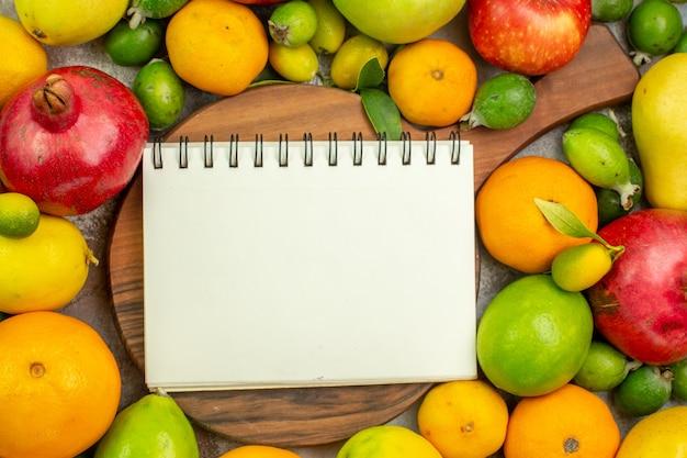 Vista de cima frutas frescas diferentes frutas maduras e maduras em um fundo branco dieta da baga saborosa cor saudável