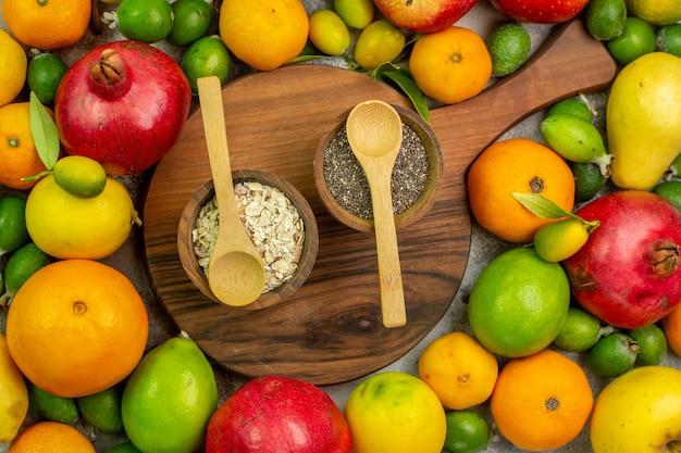 Vista de cima frutas frescas diferentes frutas maduras e maduras no fundo branco foto cor saborosa dieta baga saúde