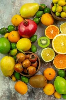Vista de cima frutas frescas diferentes frutas suaves no fundo branco árvore saborosa dieta madura cor saúde frutas cítricas