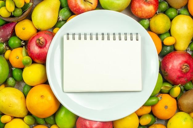 Vista de cima frutas frescas diferentes frutas suaves no fundo branco frutas maduras dieta saborosa cor árvore saúde