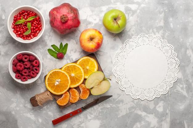 Vista de cima frutas frescas, laranjas, framboesas e romãs na mesa branca, frutas frescas suaves de vitaminas tropicais exóticas