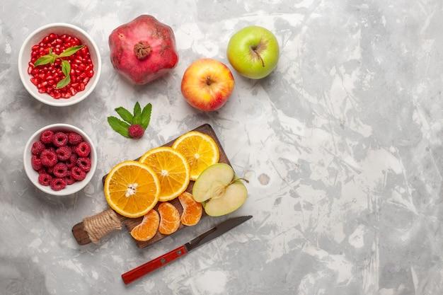 Vista de cima frutas frescas laranjas framboesas e romãs na superfície branca frutas frescas suaves vitamínicas tropicais exóticas