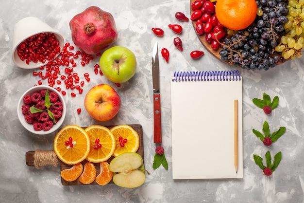 Vista de cima frutas frescas, laranjas, framboesas e romãs na superfície branca, frutas frescas sumo maduro tropical exótico