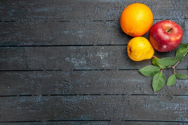 Vista de cima frutas frescas maçã pêra e laranja na mesa escura frutas frescas maduras maduras