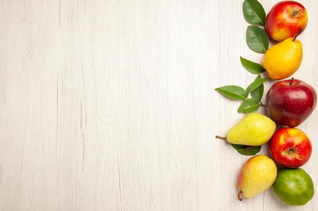 Vista de cima frutas frescas, maçãs e pêras na mesa branca, frutas maduras, cor de árvore madura, muitas frescas