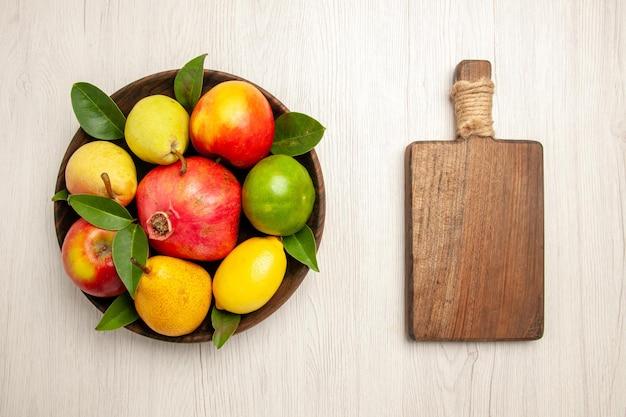 Vista de cima frutas frescas maçãs pêras e outras frutas dentro do prato na mesa branca frutas maduras árvore cor suave muitas frescas