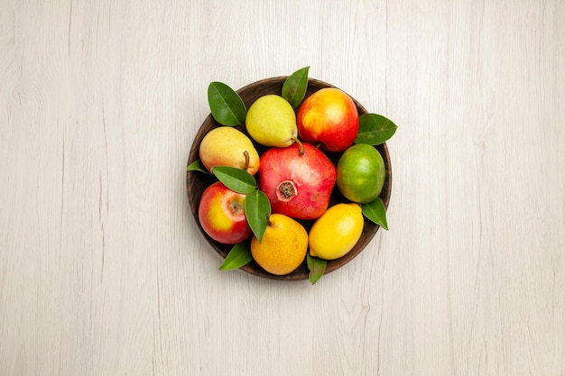 Vista de cima frutas frescas maçãs, pêras e outras frutas dentro do prato na mesa branca frutas maduras árvore cor suave muitas frescas