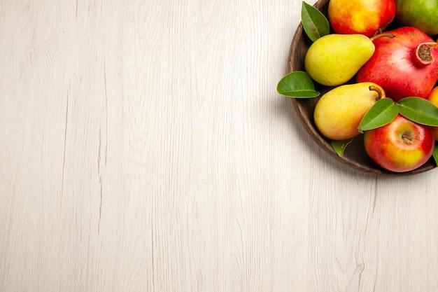Vista de cima frutas frescas maçãs peras e outras frutas dentro do prato na mesa branca frutas maduras árvore maduras muitas frescas