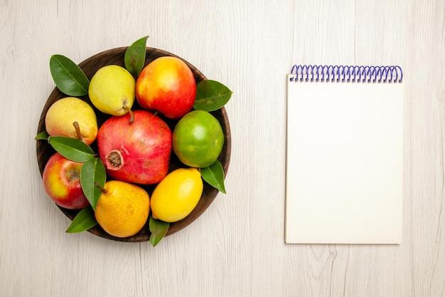 Vista de cima frutas frescas maçãs, pêras e outras frutas dentro do prato na mesa branca frutas maduras cor da árvore suave, muitas frescas