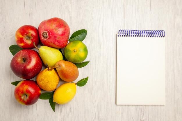 Vista de cima frutas frescas maçãs, pêras e outras frutas na mesa branca frutas maduras árvore cor suave muitas frescas