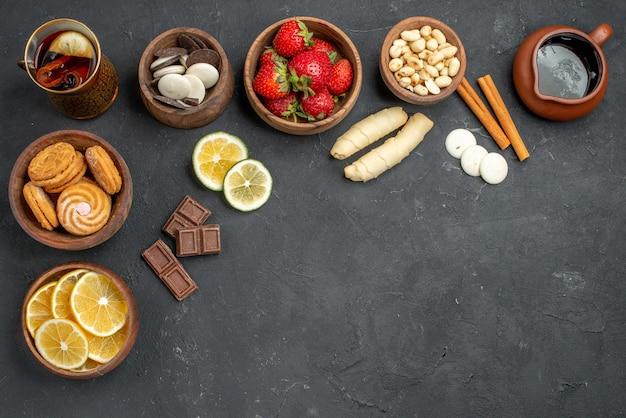 Vista de cima, frutas frescas, morangos e limões com biscoitos na superfície cinza