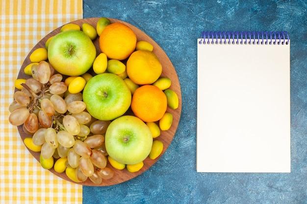 Vista de cima frutas frescas tangerinas, maçãs e uvas na mesa azul