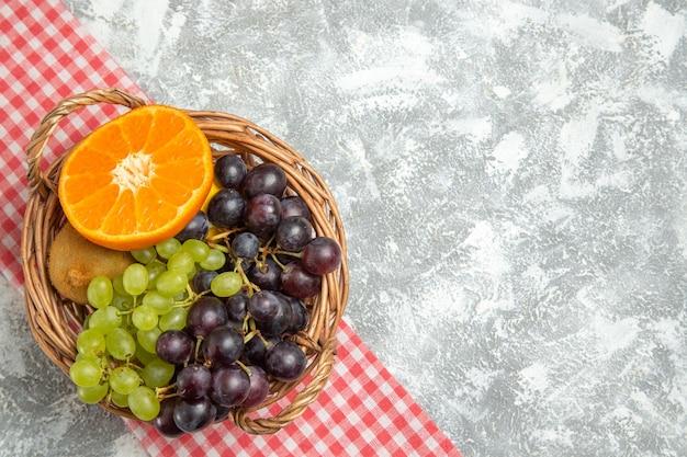 Vista de cima frutas frescas, uvas e laranjas dentro da cesta em uma superfície branca frutas maduras vitamina fresca