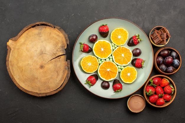 Vista de cima frutas na mesa, morangos, chocolate e frutas em tigelas de madeira, ao lado do prato de doces de laranja picados e morangos cobertos de chocolate ao lado da mesa de madeira da cozinha
