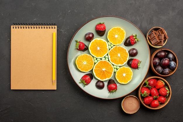 Vista de cima frutas na mesa, morangos, chocolate e frutas vermelhas em tigelas de madeira, ao lado do prato de doces de laranja picados e morangos cobertos de chocolate ao lado do caderno e do lápis