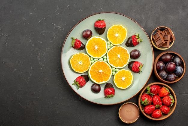 Vista de cima frutas na mesa, morangos, chocolate e frutas vermelhas em tigelas de madeira, ao lado do prato de doces de laranja picados e morangos cobertos de chocolate na mesa escura