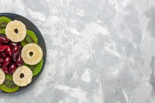 Vista de cima frutas secas anéis de abacaxi e fatias de kiwi na mesa branca frutas secas doce açúcar azedo