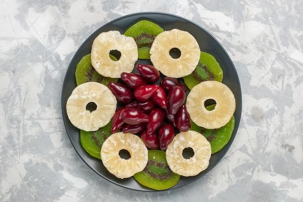Vista de cima frutas secas anéis de abacaxi e fatias de kiwi na superfície branca frutas secas doce açúcar azedo