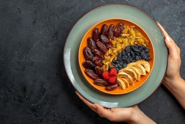 Vista de cima frutas secas com diferentes passas e salgadinhos em um espaço cinza