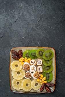 Vista de cima frutas secas fatiadas, anéis de abacaxi e kiwis no fundo cinza frutas secas passas doce azedo vitamina saúde