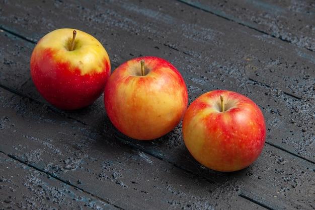 Vista de cima frutas três maçãs amarelo-avermelhadas em uma mesa de madeira cinza