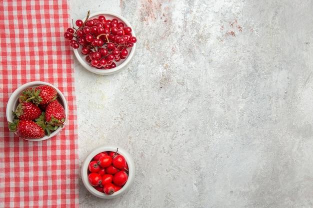 Vista de cima frutas vermelhas com frutas vermelhas na mesa branca
