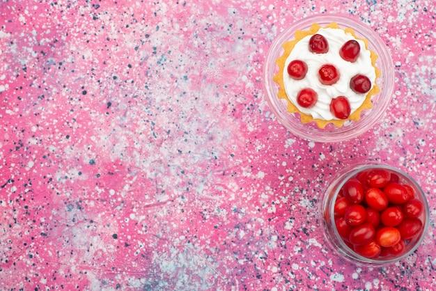 Vista de cima frutas vermelhas frescas amadurecidas, azedas e maduras dentro de um vidro transparente com bolos na mesa brilhante.
