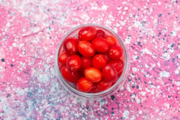 Vista de cima frutas vermelhas frescas amadurecidas, azedas e maduras dentro de um vidro transparente na mesa brilhante.