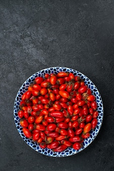 Vista de cima frutas vermelhas maduras e frutas ácidas na superfície cinza