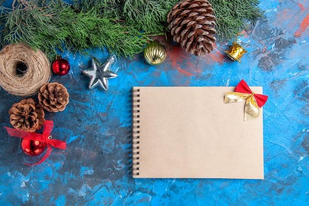 Vista de cima galhos de pinheiro com fio de palha de pinhas um caderno brinquedos de árvore de natal na superfície azul-vermelha