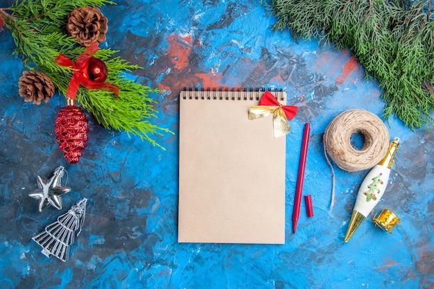 Vista de cima galhos de pinheiro com pinhas penduradas enfeites caderno caneta vermelha linha de palha na superfície azul-vermelha