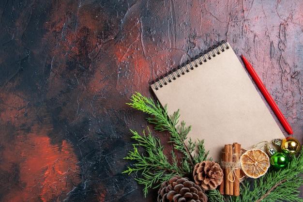 Vista de cima galhos de pinheiros e pinhas em um caderno caneta vermelha rodelas de limão secas em uma superfície vermelha escura.