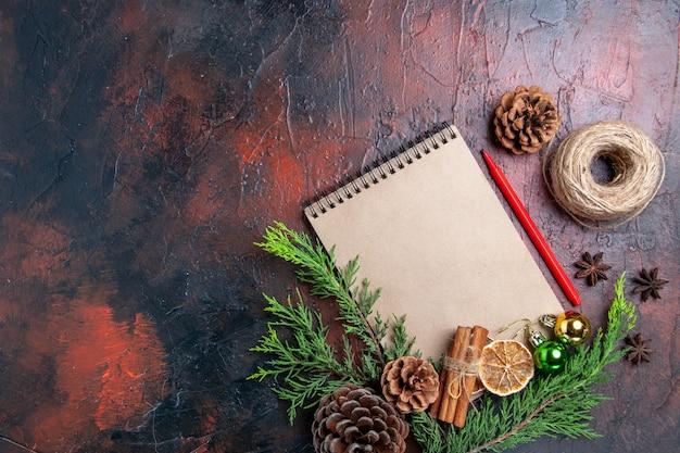 Vista de cima galhos de pinheiros e pinhas em um caderno caneta vermelha seca fatias de limão linha de palha em superfície vermelha escura com espaço livre