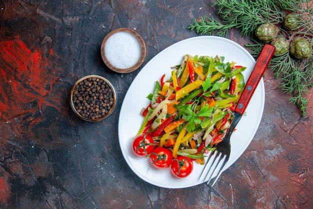 Vista de cima, garfo de salada de vegetais em prato oval, especiarias diferentes em pequenas tigelas na mesa vermelha escura