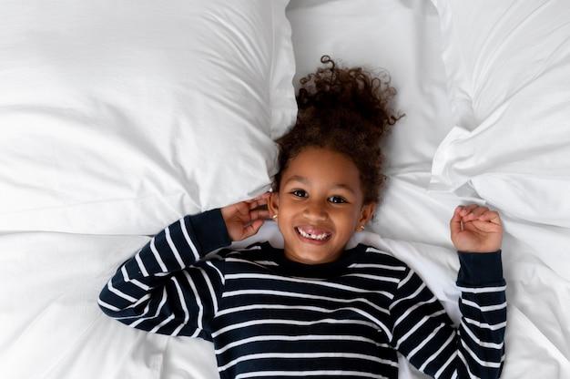 Vista de cima, garota feliz na cama