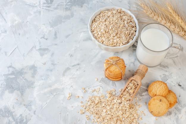 Vista de cima garrafa de leite e biscoitos de vidro de leite tigela de aveia espigas de trigo em fundo cinza cópia local