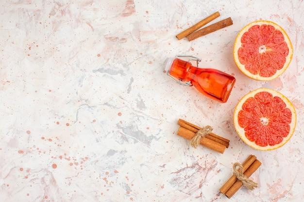 Vista de cima garrafa de toranjas cortadas em paus de canela na superfície nua com espaço de cópia