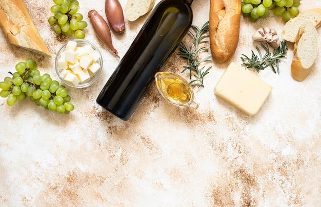 Vista de cima garrafa de vinho branco, uvas, queijo, manteiga e baguete