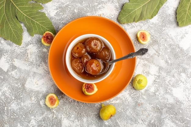 Vista de cima, geléia de figos doces com figos frescos em um prato de laranja na mesa branca
