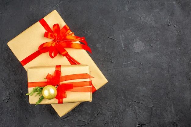Vista de cima, grandes e pequenos presentes de natal em papel pardo amarrado com fita vermelha em fundo escuro.