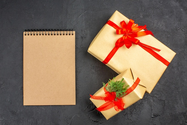 Vista de cima, grandes e pequenos presentes de natal em papel pardo amarrado com fita vermelha, um caderno em fundo escuro