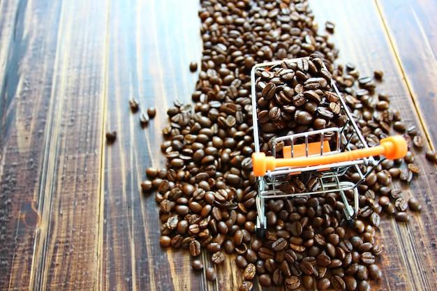 Vista de cima grãos de café torrados em um carrinho de compras pequeno em grãos de café em um espaço de cópia de piso de madeira retrô