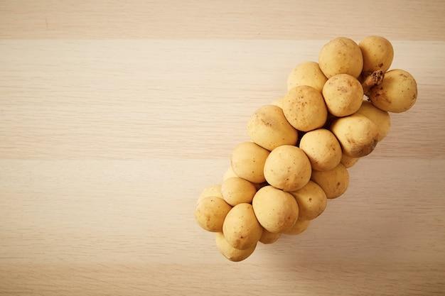 Vista de cima grupo de longkong é uma fruta do sul da ásia tailandesa na mesa de madeira copie o espaço para o texto