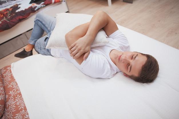 Vista de cima homem abraçando uma almofada, deitado em uma cama, relaxando em casa