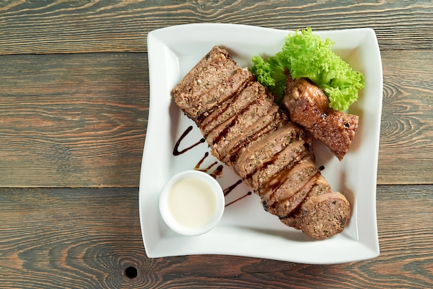 Vista de cima horizontal, tiro de carne fatiada em um prato quadrado branco na mesa de madeira copyspace comer comida receita jantar refeição almoço ceia assado molho verdes decorados.