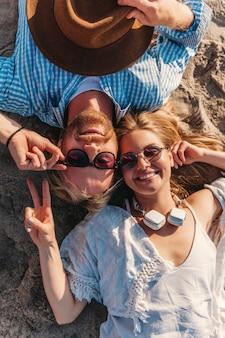 Vista de cima, jovem atraente, sorridente, feliz, homem e mulher com óculos de sol, deitado na praia de areia