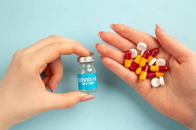 Vista de cima jovem mulher com comprimidos nas mãos sobre fundo azul pandemia de vírus covide saúde cor laboratório de ciências hospital